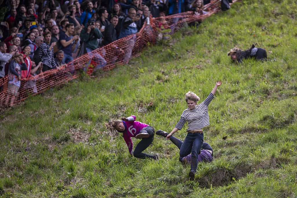 Throw yourself off the top': daredevils enter cheese-rolling race - CGTN
