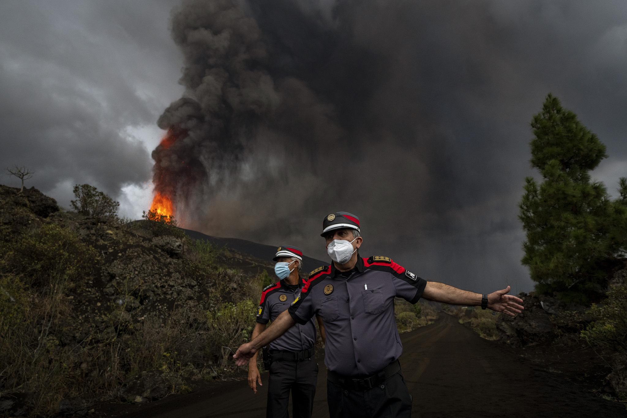 Policiais ordenam que os jornalistas se afastem da área de risco, na ilha de La Palma. (Foto Reprodução/CFP)