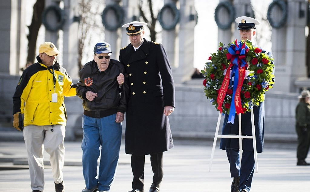 A National Park Service volunteer escorts Retired Air Force Staff Sgt. Bill  Hare, 91, as he places a wreath during a ceremony held by the Friends of  the ...